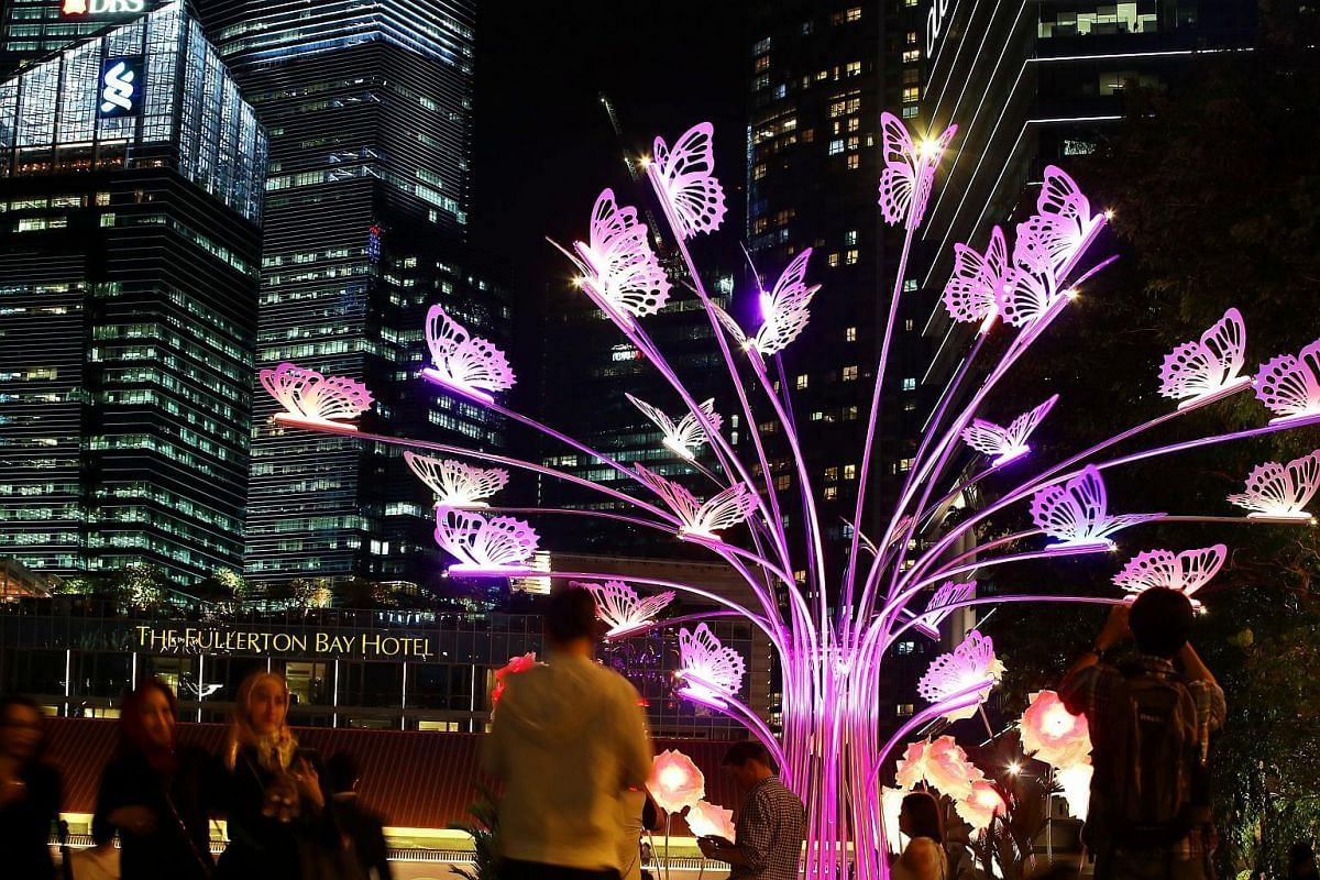 People walking by an illuminated structure resembling a tree forming part of an installation titled The Colorful Garden Of Light during a media preview of the iLight Marina Bay Festival in Singapore, on March 1, 2017.