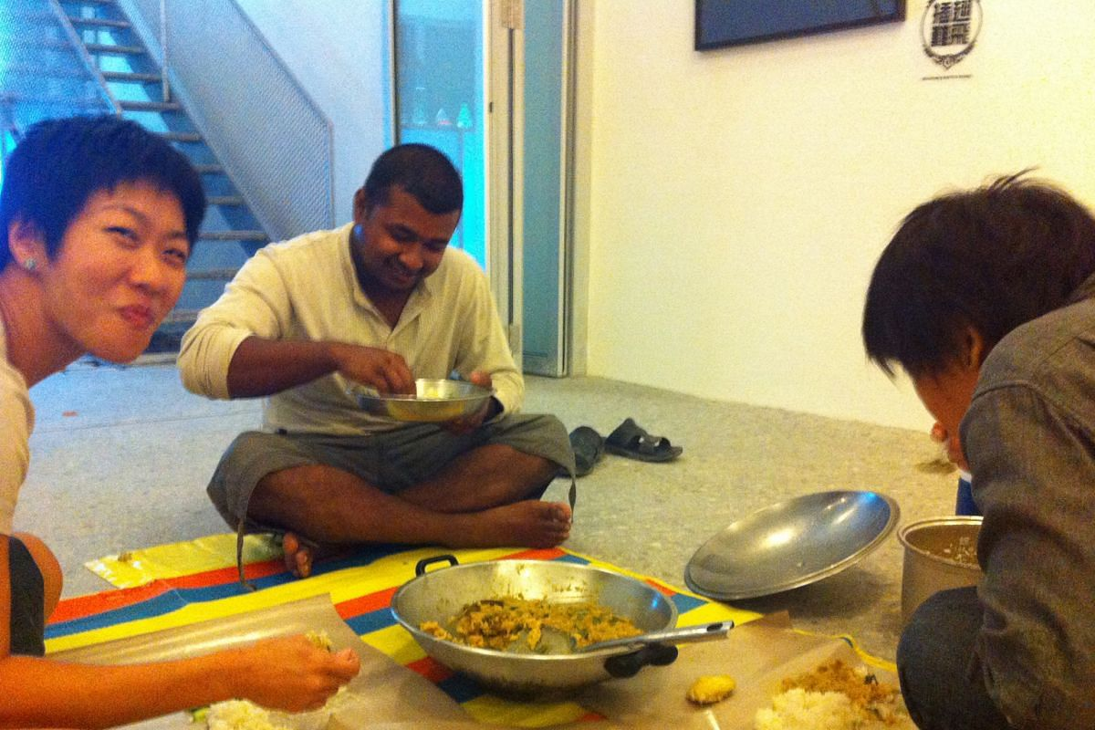 My Life So Far: Ms Tan (left) having dinner with Bangladeshi worker Ibrahim in 2012 at the Lorong 24A Shophouse Series art show. On the right is writer Amanda Lee Koe.