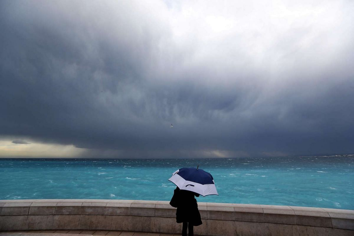 A woman looks at an approaching storm on March 6, 2017, in Nice, southeastern France.