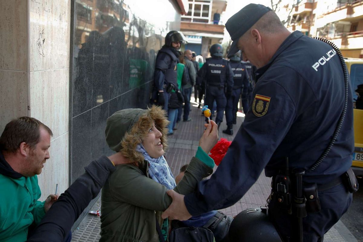 An anti-eviction activist offers a lollipop to a Spanish riot policeman in Parla, Spain March 6, 2017.