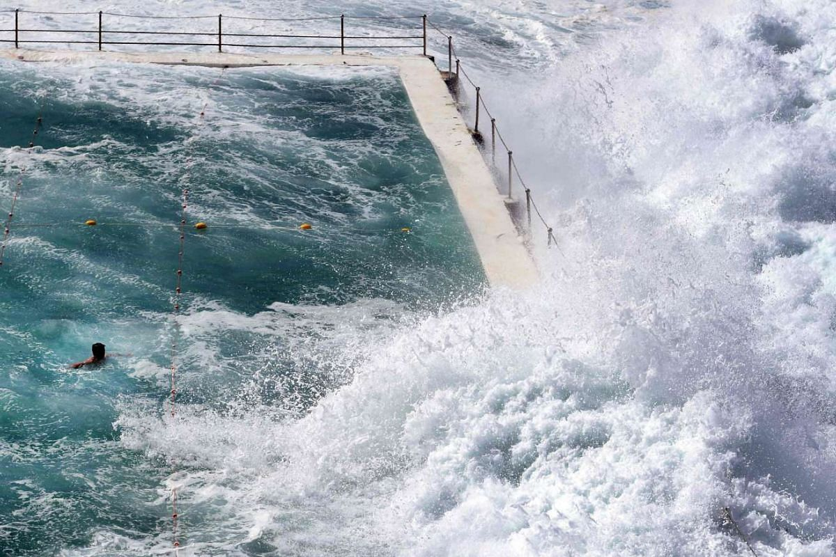 A swimmer at Bondi's ocean pool watches as a big wave pours into the pool as large seas pound the coast at Bondi Beach in Sydney on March 6, 2017.