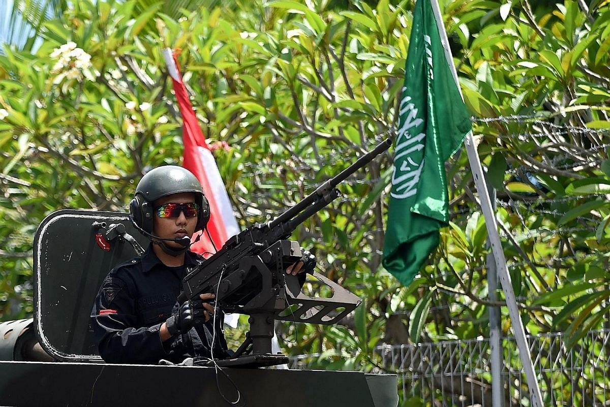 King Salman, in the front car, arriving on Saturday in Bali, where he is on holiday till Sunday. In Indonesia, his motorcade includes several armoured vehicles, his personal bodyguards and Indonesian troops. A soldier on alert in an armoured personne