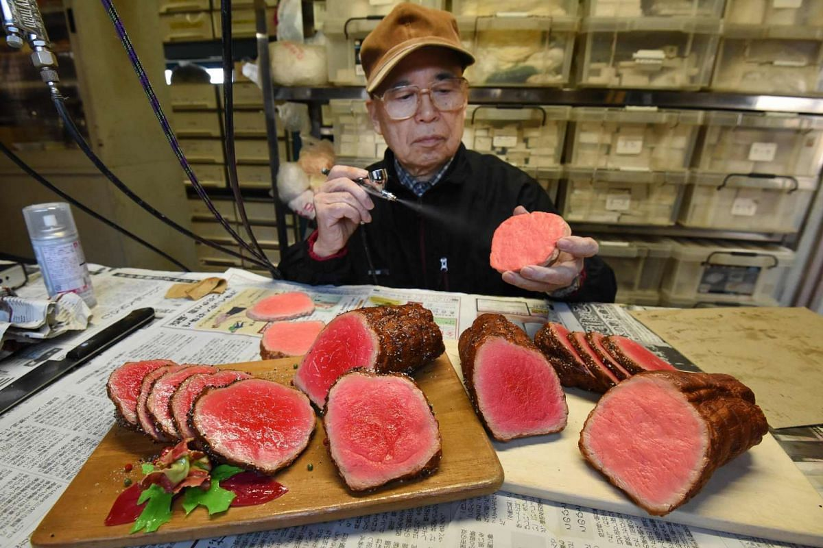 Mr Noriyuki Mishima, a craftsman at Fake Food Hatanaka, spraying paint on a plastic food replica.