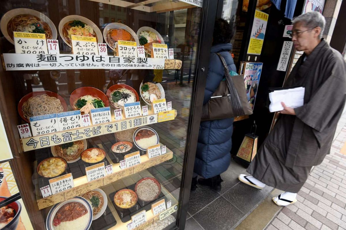 Customers entering a Japanese restaurant with a presentation of fake food dishes displayed in front of the eatery in Tokyo.