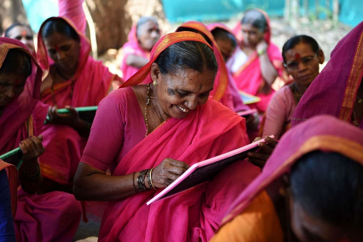 Indian grandmother Savita Deshmukh (centre), 62, during class where students are taught to read simple text and practise writing their names on their slates.