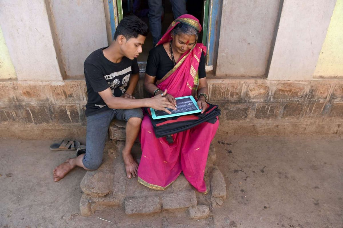 Aniket Kedar, 15, helping his grandmother, Gulab Kedar, complete her homework.