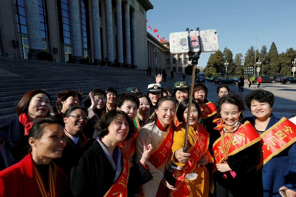 A group of awardees pose for a photo before a Women's Day awards ceremony on Tuesday (March 7) outside the Great Hall of the People in Beijing where sessions of the National People's Congress are taking place. All-China Women's Federation president S