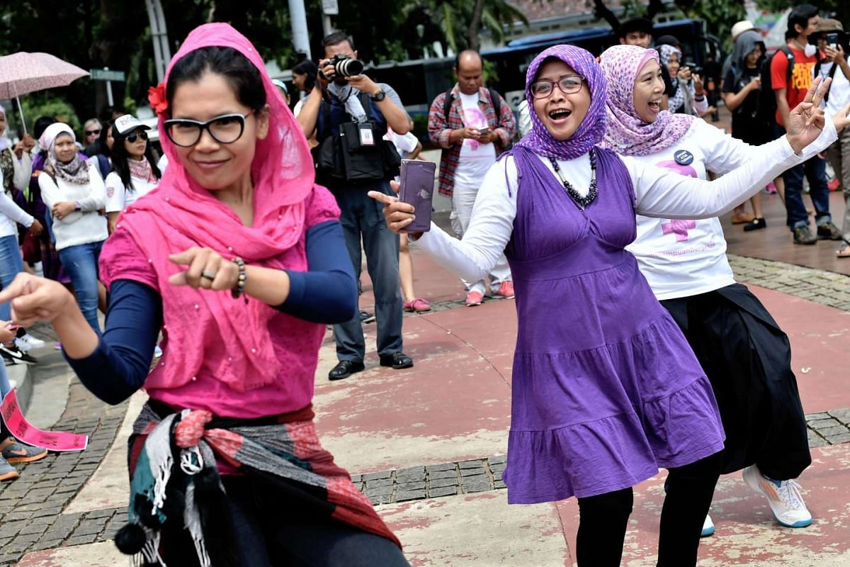 Dancers perform at a rally in Jakarta, Indonesia, organised by 33 women's rights organisations, which saw hundreds of women dressed in pink and purple march towards the State Palace.