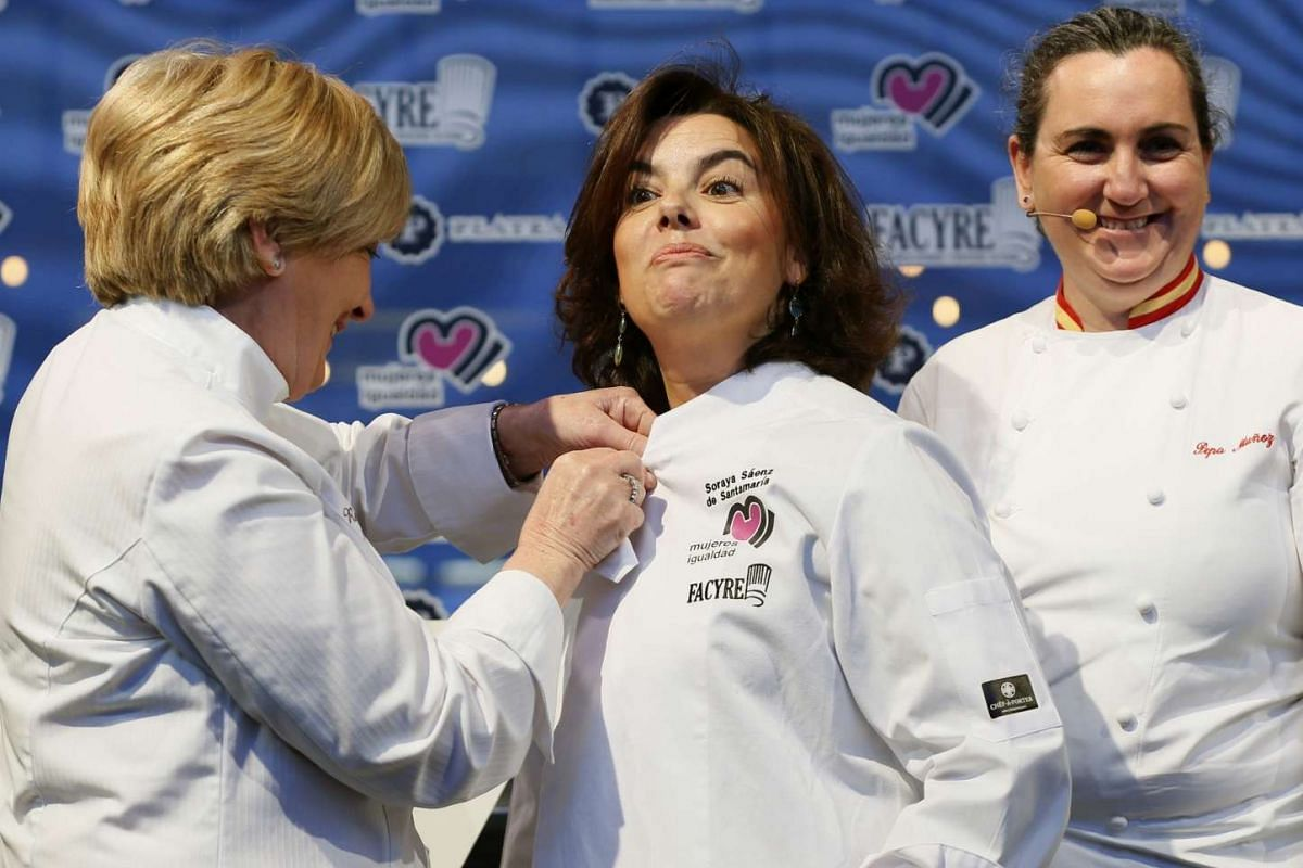 Vice-Prime Minister Soraya Saenz de Santamaria puts on a chef garment with the aid of Spanish chefs Pilar Idoate (left) and Pepa Munoz at the closing ceremony of the Gastronomy Is Feminine event on Monday (March 6) in Madrid, Spain. Marches are also