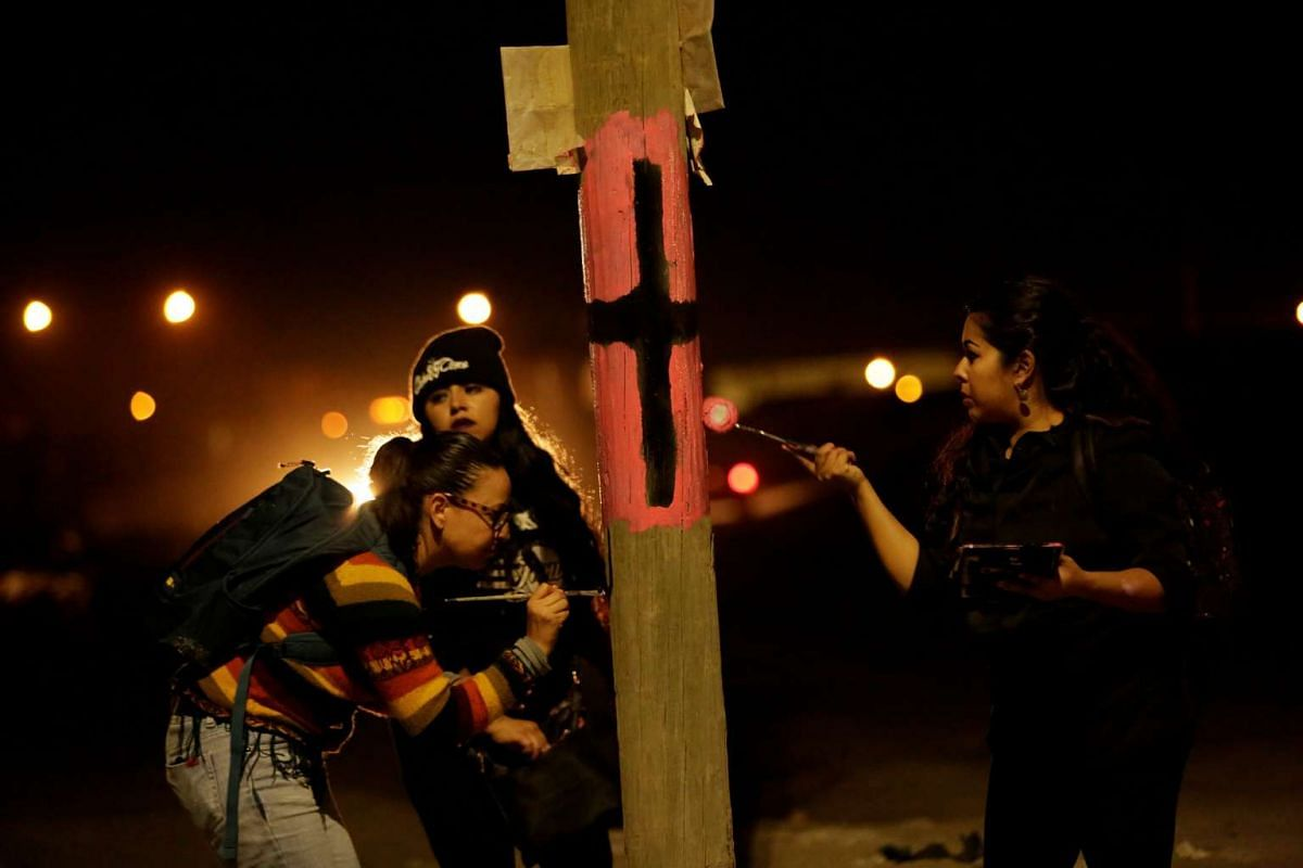 Activists paint a black cross on a lamp post to remember women who have gone missing or been killed in Ciudad Juarez, Mexico. Since the early 90s, hundreds of young women, some as young as 12 years old, have been raped, strangled and mutilated. Their