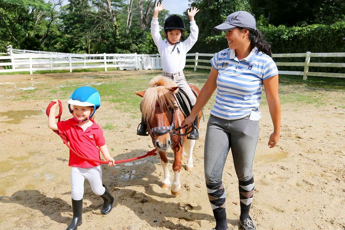 Lucie Leonard (left), 21/2, and Zara Oking, five, having a horseriding class with their instructor, Ms Nadia Chen, at National Equestrian Centre.