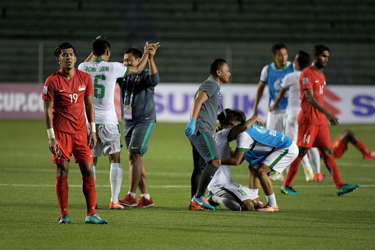 Singapore's striker Khairul Amri (left, in red) looking dejected as Indonesian players (in white) celebrate their 2-1 win after the final whistle of the Asean Football Federation (AFF) Suzuki Cup Group A decider match at the Rizal Memorial Stadium