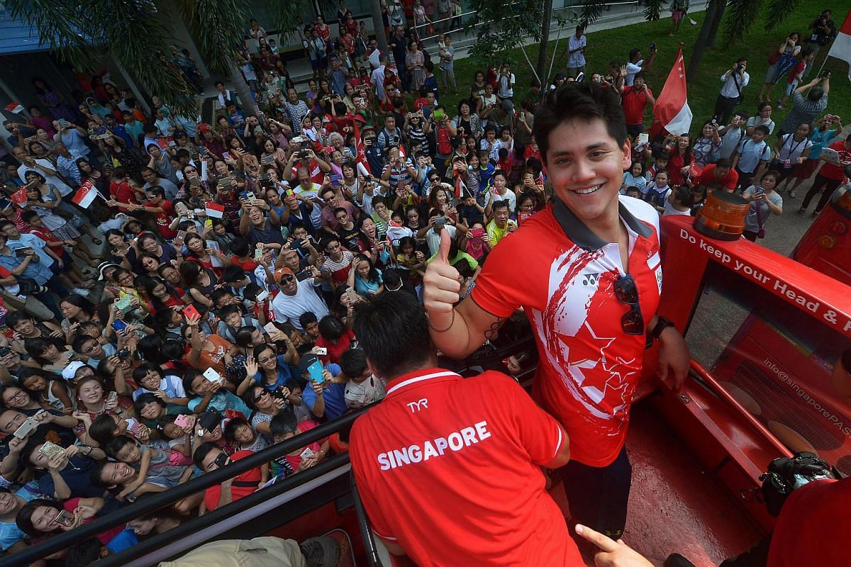 Singapore's first Olympic champion Joseph Schooling atop the victory bus on Aug 18, 2016. He made history when he won the nation's first gold medal in the 100m butterfly in Rio.