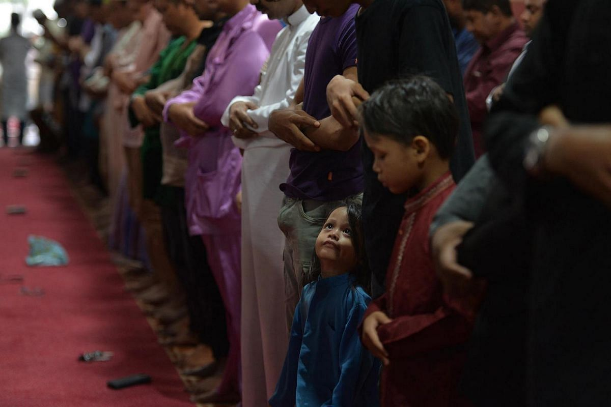 A young boy watches as worshippers say their morning prayers at the En-Naeem Mosque in Hougang to mark Hari Raya Haji on Sept 12, 2016.