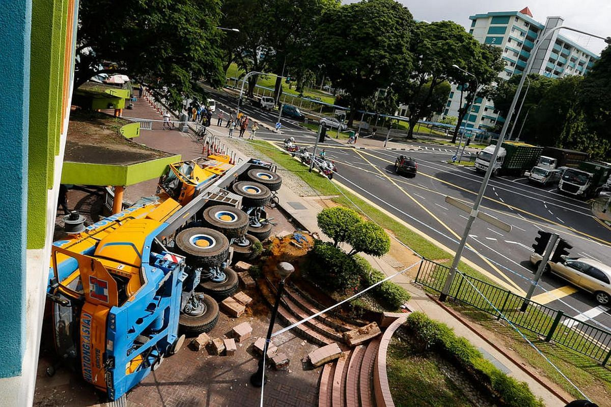 A mobile crane lies on its side after it piled into a Woodlands Housing Board block when its driver lost control at a junction on Feb 24, 2016.