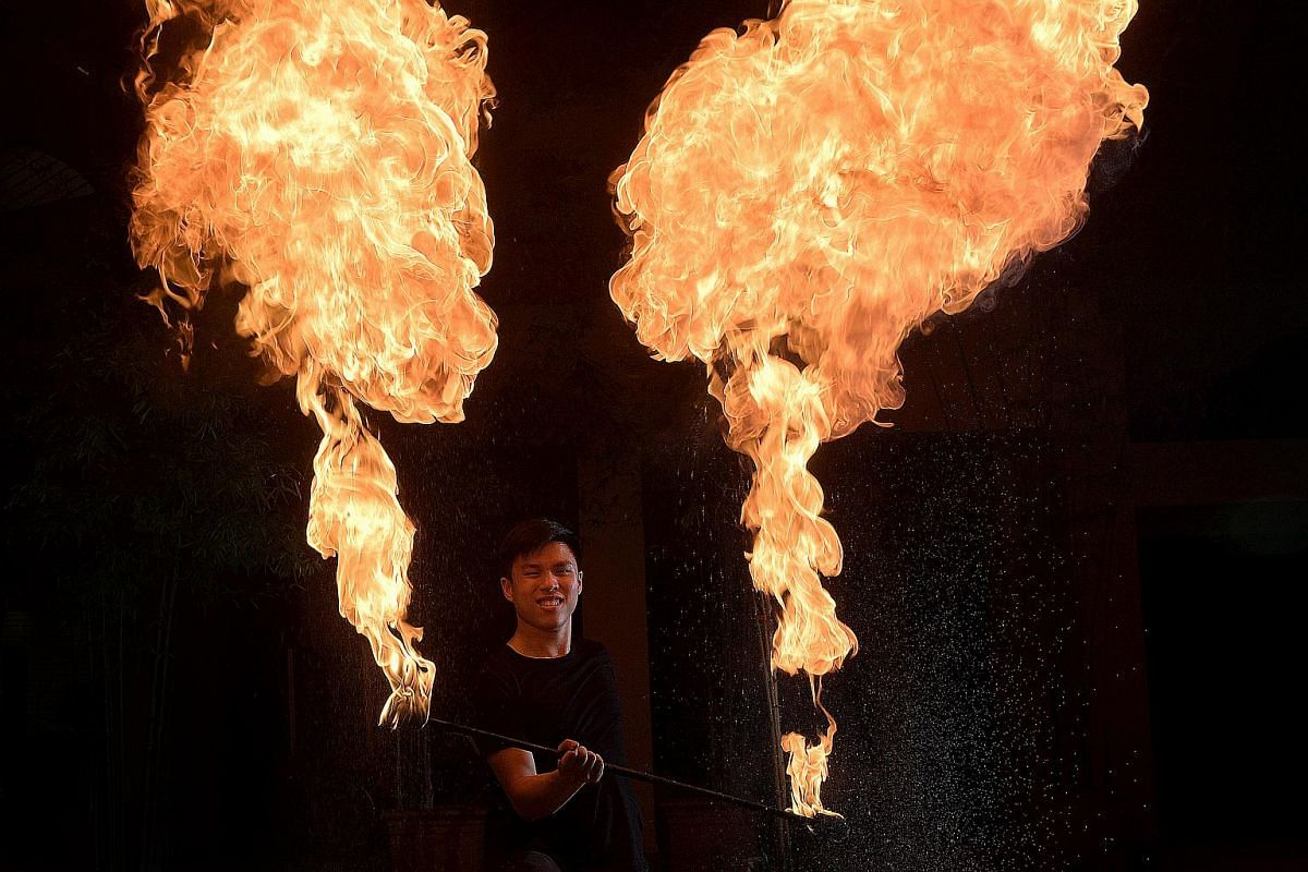 Mr Jonathan Goh shows off his fire-spinning skill in the courtyard of Kallang Community Club on Nov 22, 2016. He is part of the busker pair, Annoying Brothers, who perform circus acts as part of their shows.