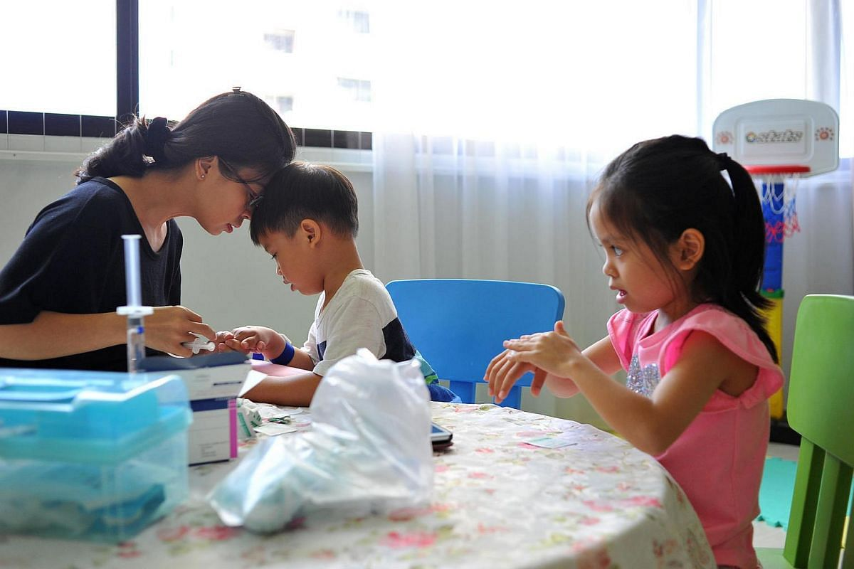 Mrs Anne Loh praying with her son, James, on June 7, 2016, for a smooth infusion, before giving him a dose of clotting factors, which are proteins that control bleeding. The four-year-old has severe haemophilia, a rare inherited blood disorder. The c