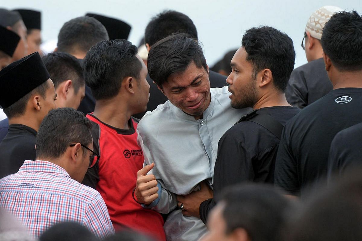 A grieving Muhammad Hatin Kamil (in light-grey top), who was a witness to the accident at Pasir Ris MRT station which killed two of his SMRT colleagues, at their burial at the Muslim cemetery in Lim Chu Kang on March 23, 2016.