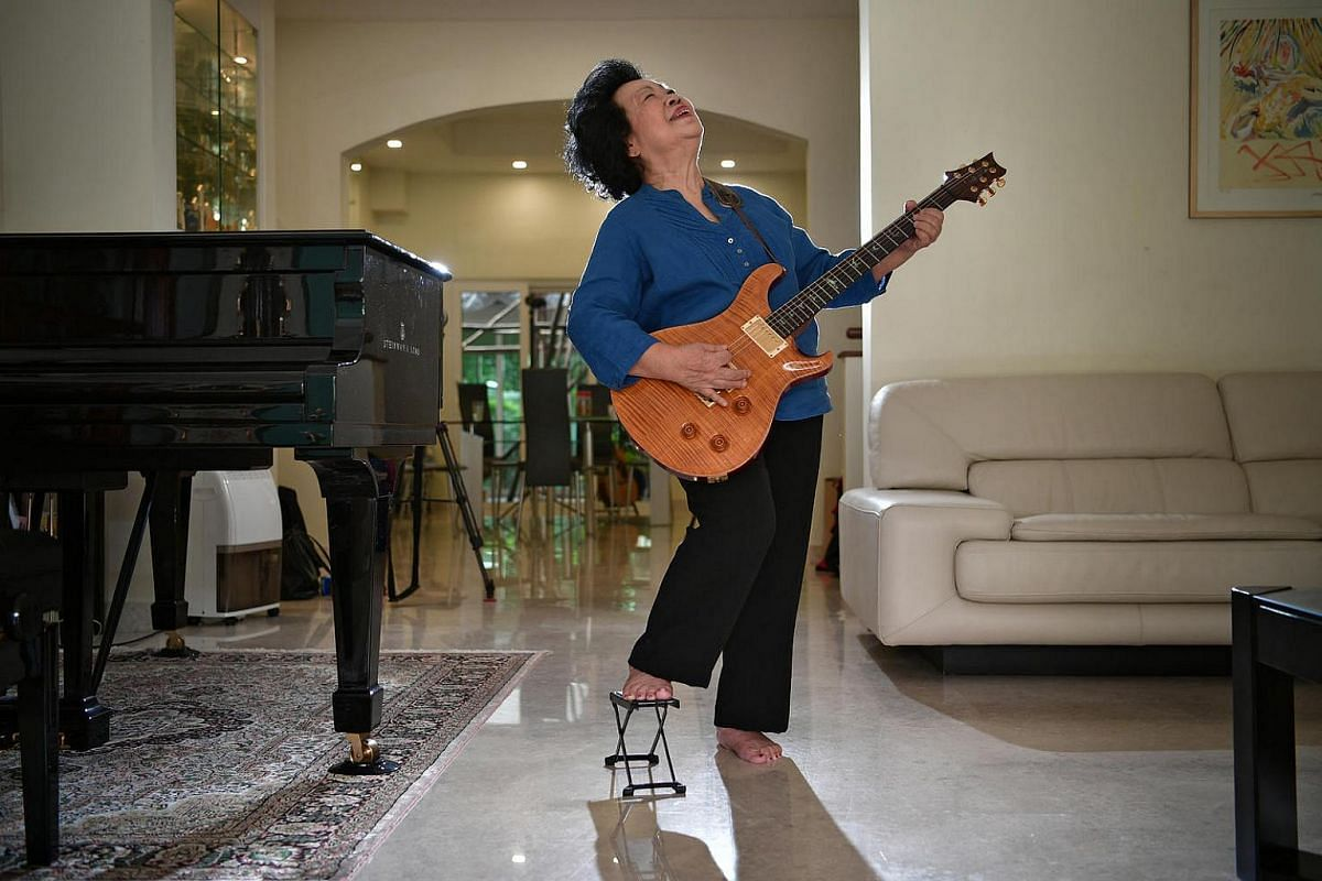Madam Mary Ho posing with her electric guitar at home on Nov 22, 2016. Her first guitar lesson started with Santana's Samba Pa Ti and she now performs pro bono at charity events.