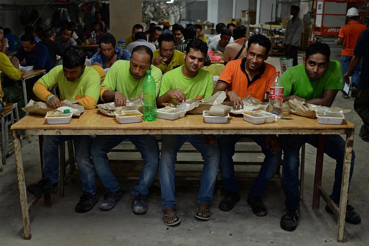 Workers from Unison Construction having their lunch at their worksite on May 11, 2016. Unison is one of three firms participating in a pilot programme run by social enterprise 45Rice that ensures hot meals are delivered to foreign workers thrice a da