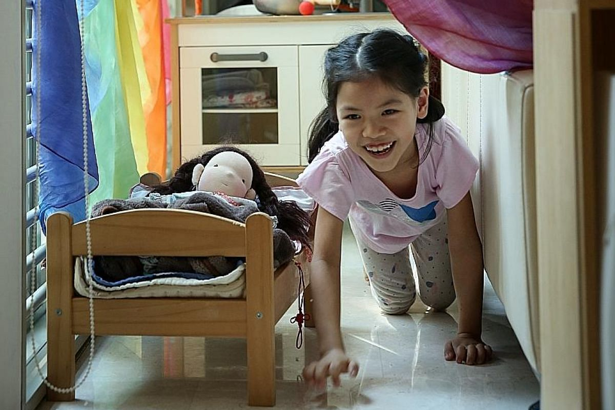 Eight-year-old Ng Xi Lin in the makeshift play area behind the living room sofa in her home.