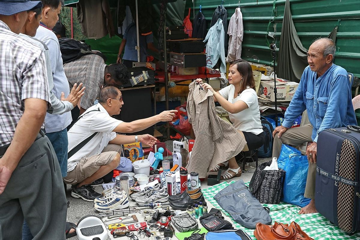 Straits Times journalist Melody Zaccheus selling items, donated by her colleagues, at the Sungei Road flea market on Feb 25. Profits go to the ST School Pocket Money Fund.