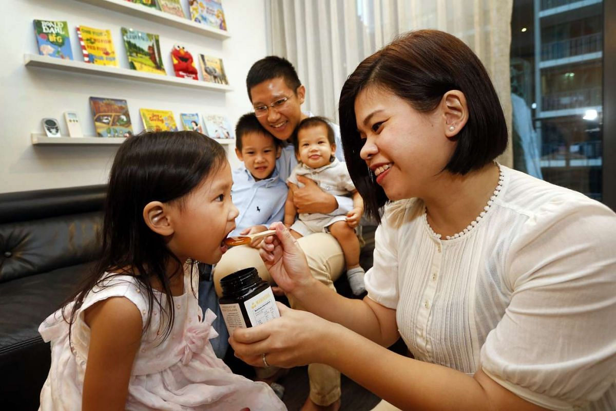 Mrs Rachel Fong giving her daughter, Victoria, three, a teaspoon of Manuka honey. Her husband, Mr Fong Xiongkun, 32, and their sons, Micah, five, and Mark, nine months, are in the background.
