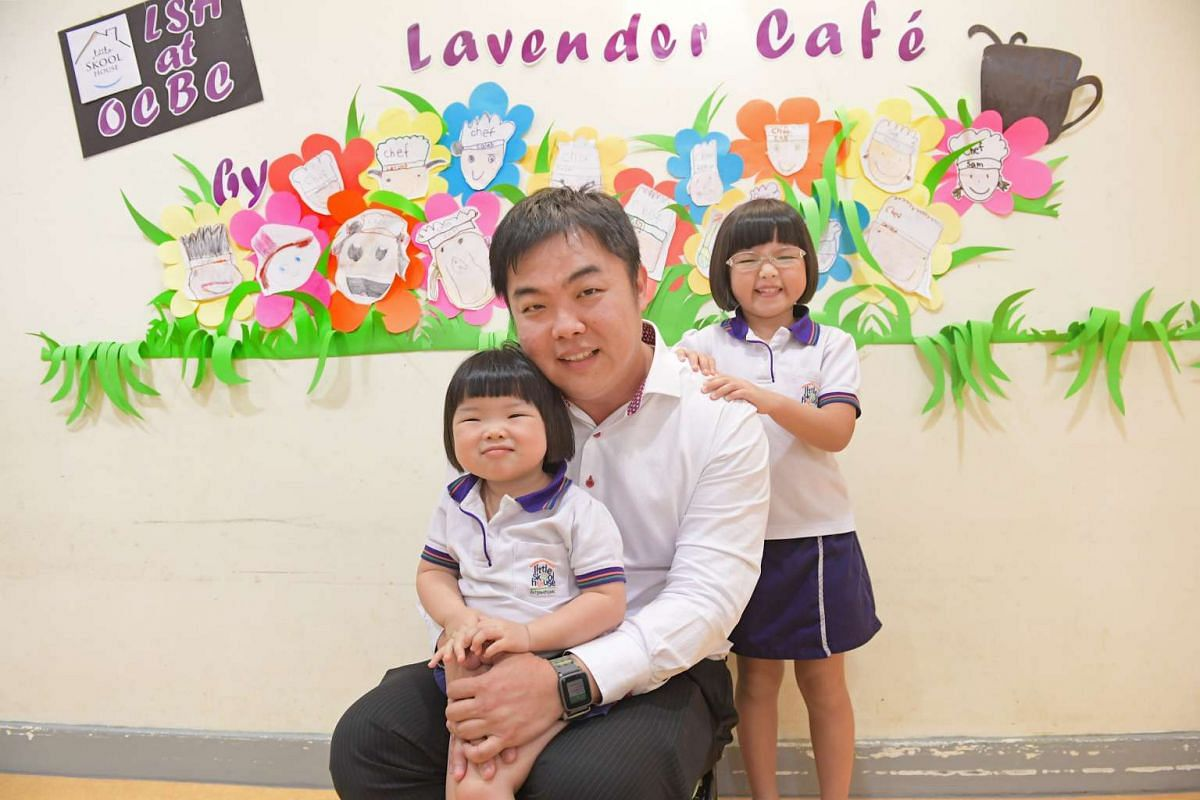 Mr Kenny Ng, 39, an assistant vice-president at OCBC Bank, with his daughters Clarissa (with glasses), six, and Clariel, three. They attend the in-house childcare centre at his workplace.