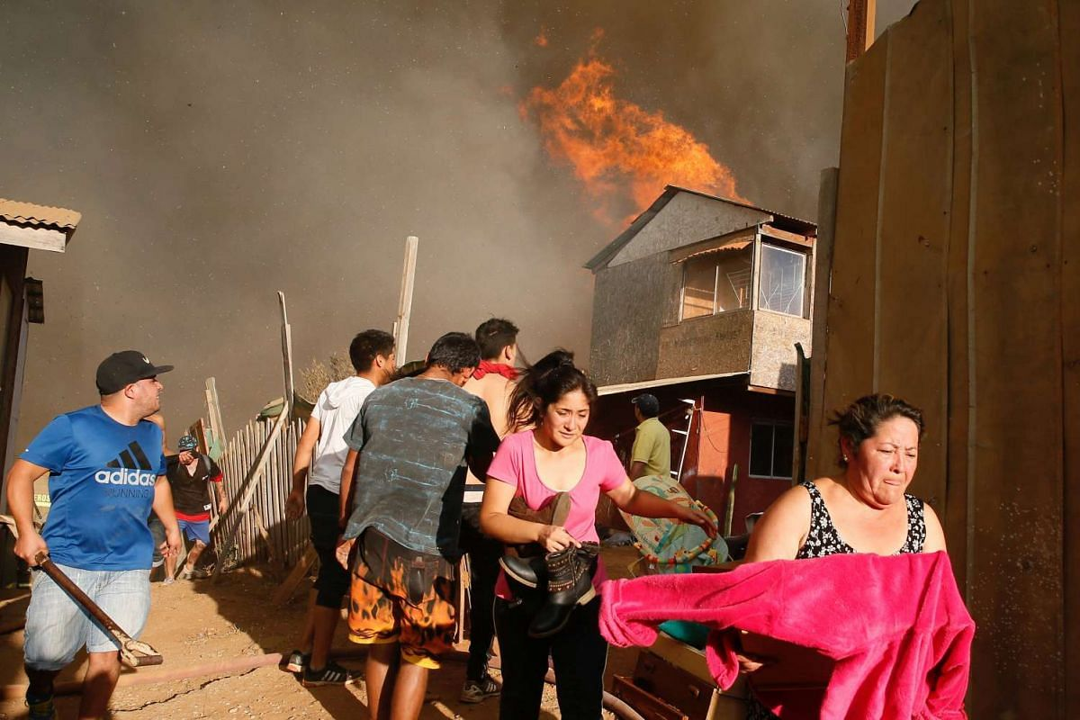 Residents flee with their belongings from a burning house during a wildfire in Vina del Mar, Chile, March 12, 2017. PHOTO: REUTERS