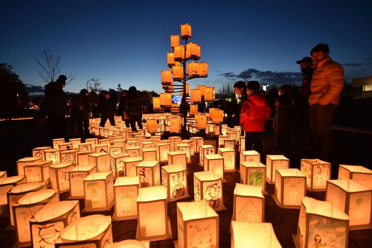 Visitors look at paper lanterns as part of a memorial service for victims of the 2011 quake-tsunami disaster in Natori, Miyagi prefecture on March 11, 2017. PHOTO: AFP