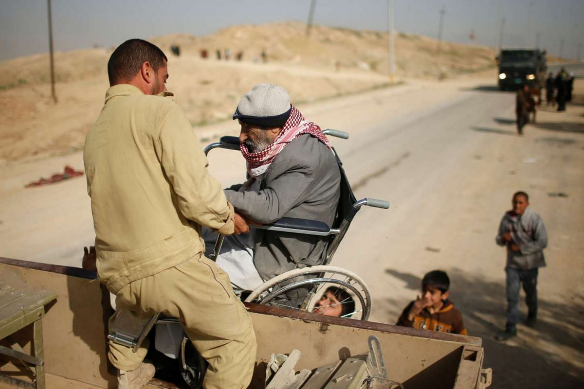 An Iraqi soldier helps a displaced Iraqi man onto a truck to be carried to a safe place, as Iraqi forces battle with Islamic State militants, in western Mosul, Iraq March 12, 2017. PHOTO: REUTERS