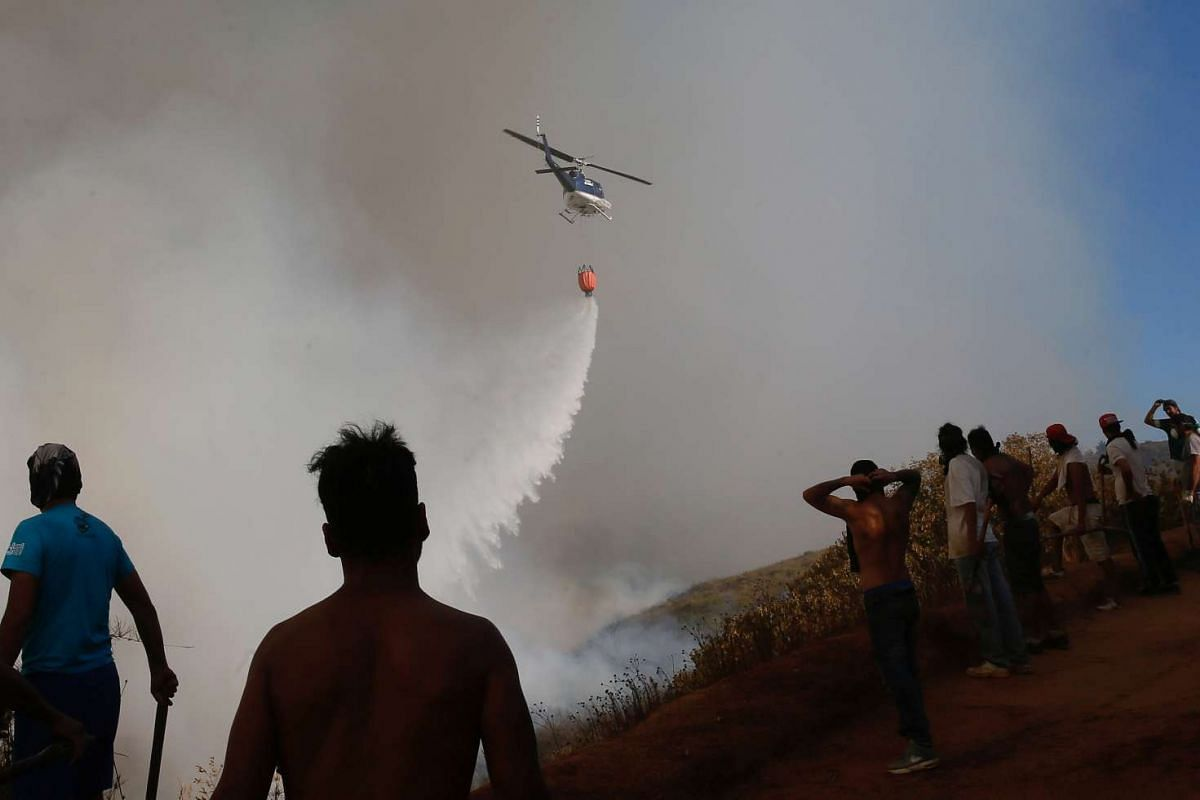 A helicopter makes a water drop to prevent a wildfire from spreading to homes in Vina del Mar, Chile, on March 12, 2017.
