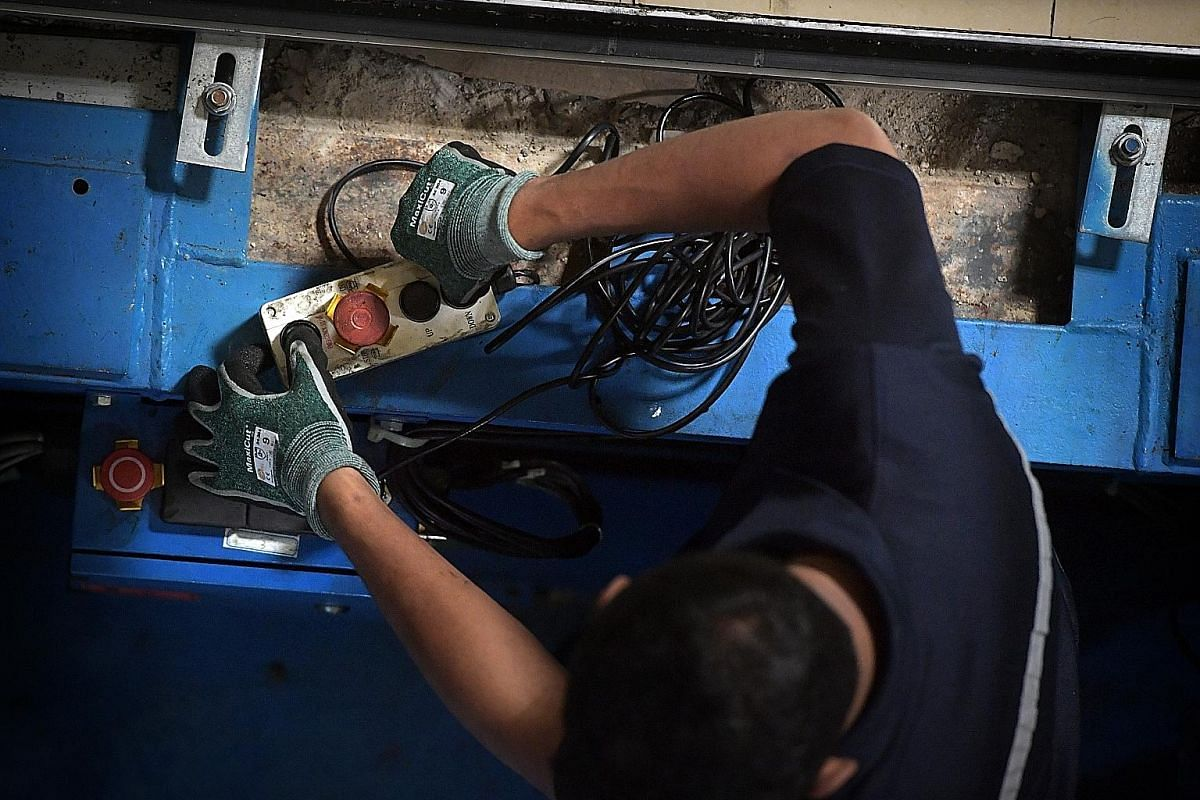 Technician Mohd Iskandar Mohamad Sopi inflating a high-voltage glove to check it for tears or leaks before putting it on. This insulated glove, part of his personal protection equipment, prevents accidental electrocution on the job. Lifts are run on