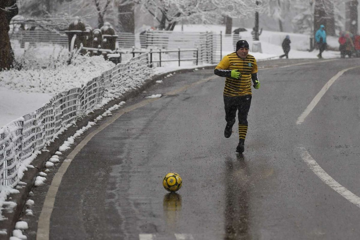 A man kicks a soccer ball down the street as he runs in the snow in Central Park, New York, on March 10, 2017.