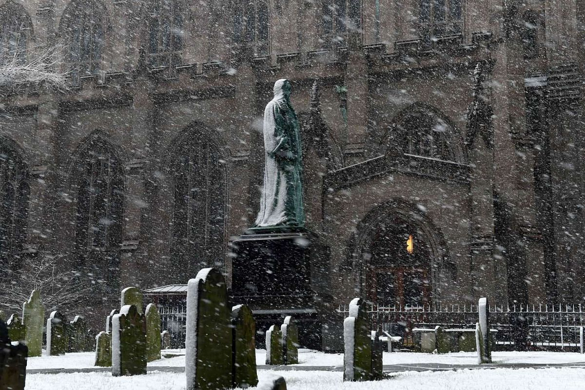 Blowing snow falls on a statue outside of Trinity Church on Wall Street in New York on March 10, 2017.