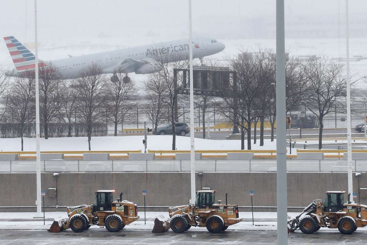An American Airlines plane departs during the snowstorm at O'Hare International Airport in Chicago, Illinois, on March 13, 2017. Some areas received up to about 12cm of snow and more than 400 flights were cancelled at O'Hare.