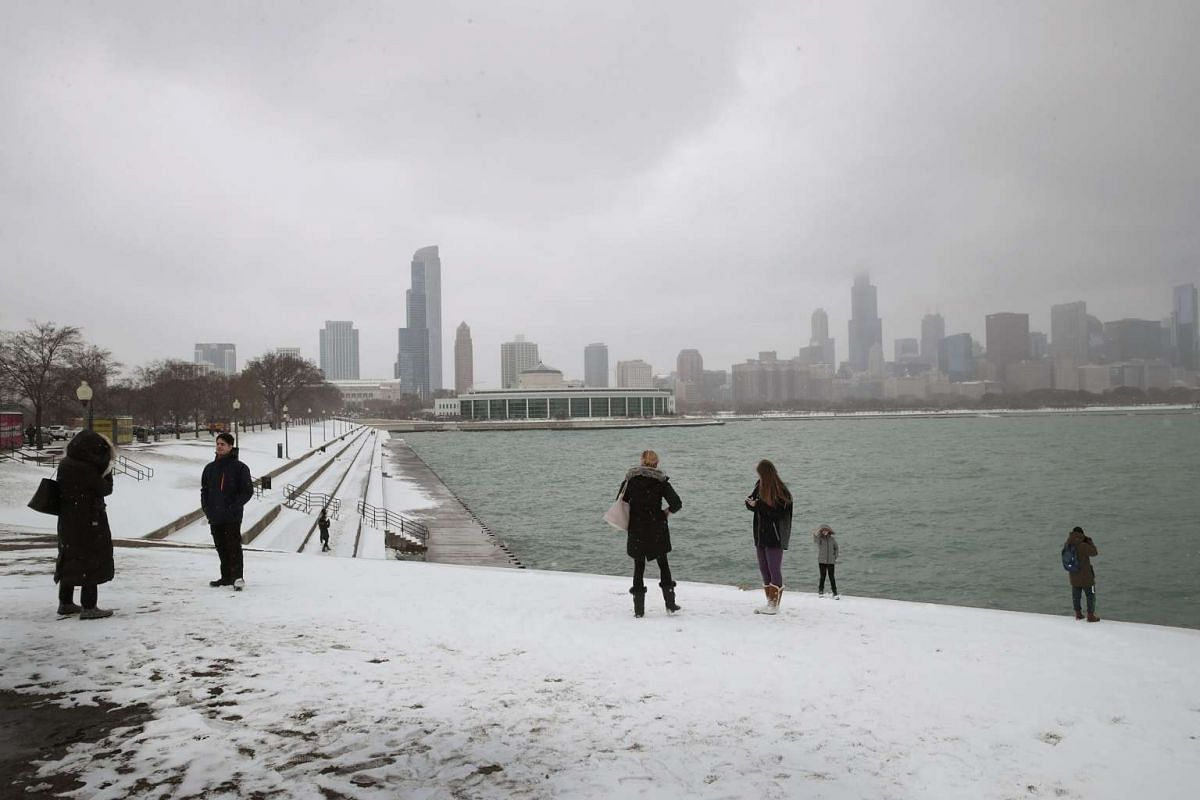 People walk along a snow-covered lakefront near downtown in Chicago, Illinois, on March 13, 2017.