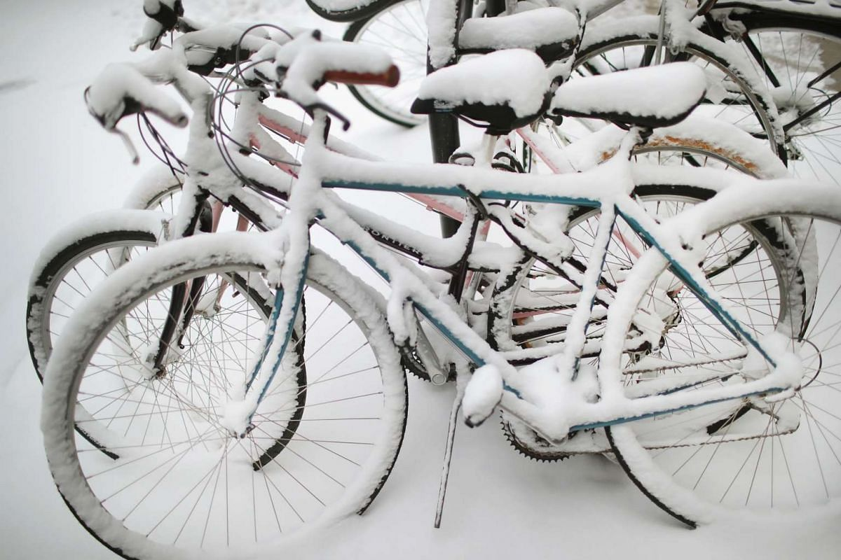 Snow covers bicycles parked near the campus of the University of Chicago in Chicago, Illinois, on March 13, 2017.