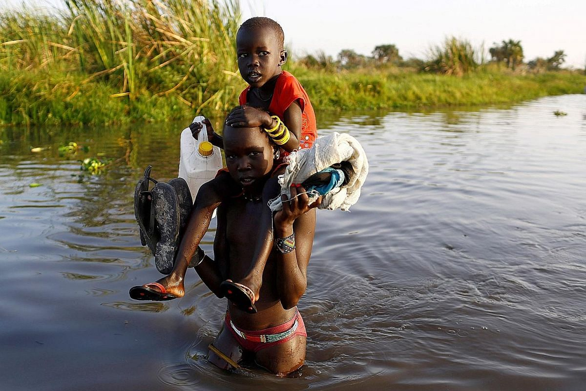 Children crossing a swamp to reach a registration area before a United Nations food distribution programme came to their aid in Thonyor, South Sudan, last month. Food sacks airdropped by a WFP plane in South Sudan last month, bringing relief to hard-