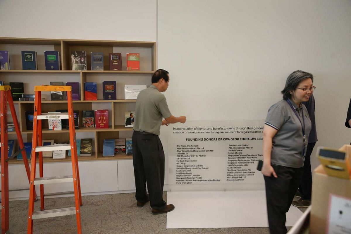 Staff preparing the installation of a sign of appreciation for the founding donors of the Kwa Geok Choo Law Library.
