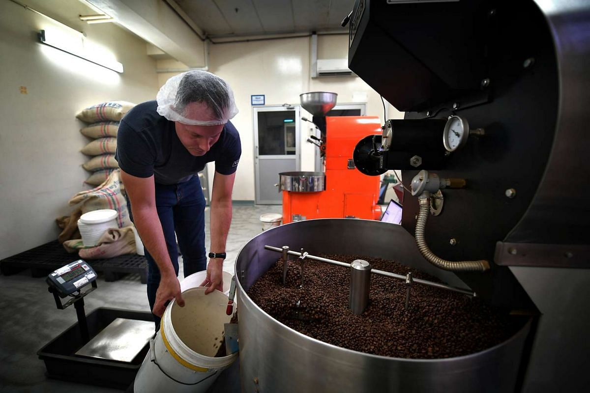 Mr Casey Blanche, head roaster of Singapore cafe Oriole Coffee + Bar, discharging cooled-down roasted beans for packaging. Oriole buys premium coffee beans from Indonesia.