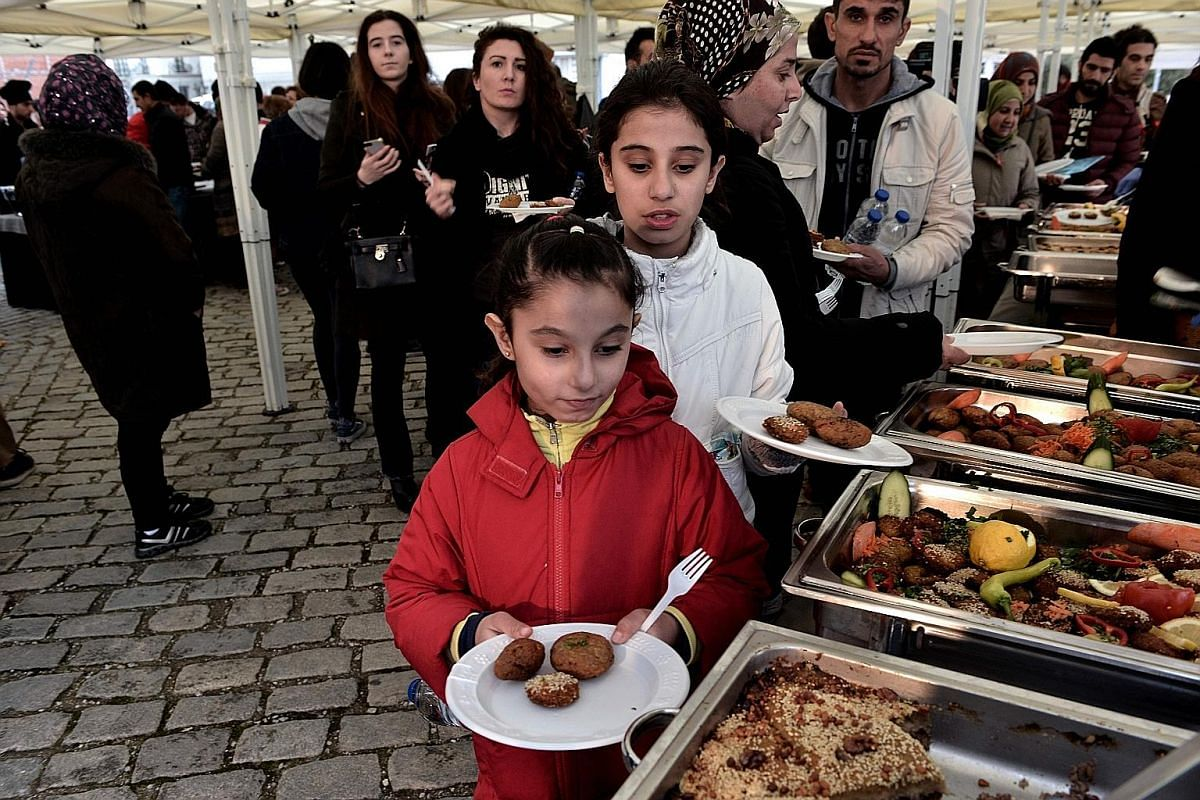 A Syrian playing a qanun, a traditional trapezoidal wooden stringed instrument. A meal cooked by refugees - some from Iraq and Syria - at a Food Uniting People #With Refugees event in the port of Thessaloniki, Greece, on March 10. Among the things Sy