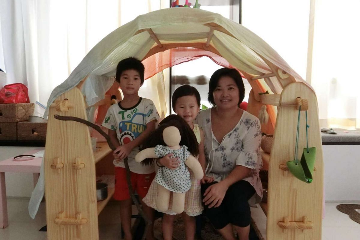 Ms Queenny Choong with her son Yun Wei and daughter Yun Ee, who is holding a doll made by Ms Choong using natural materials. They are inside a playhouse made of wood without nails.
