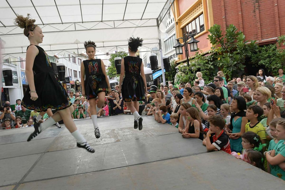 Festival goers at the St. Patrick's Day Street Festival watch traditional Irish dancers perform on a stage set up at the junction of Circular Road and Canton Road on March 19, 2017.