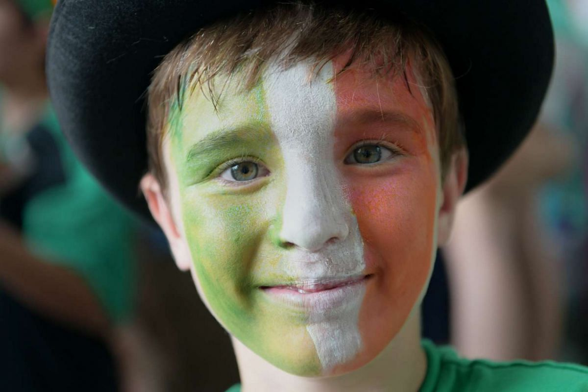 A boy with the Irish flag painted onto his face smiles during the St. Patrick's Day street festival on March 19, 2017.