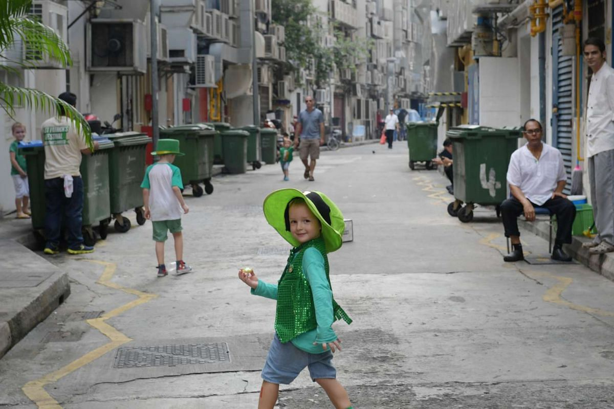 A boy walks along the back alley near Boat Quay during the St. Patrick's Day street festival on March 19, 2017.