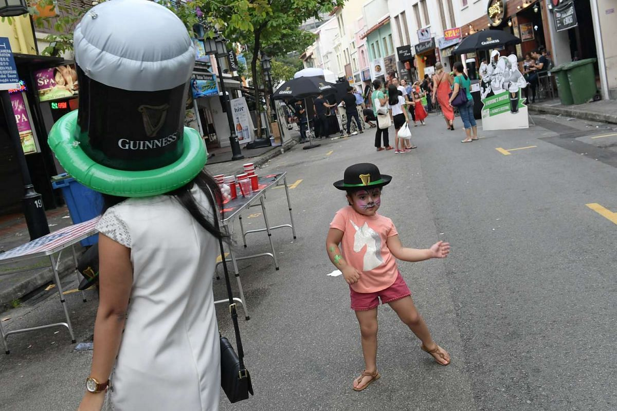 Three-year-old Shanaya Mitra dances along Circular Road during the St. Patrick's Day street festival on March 19, 2017.