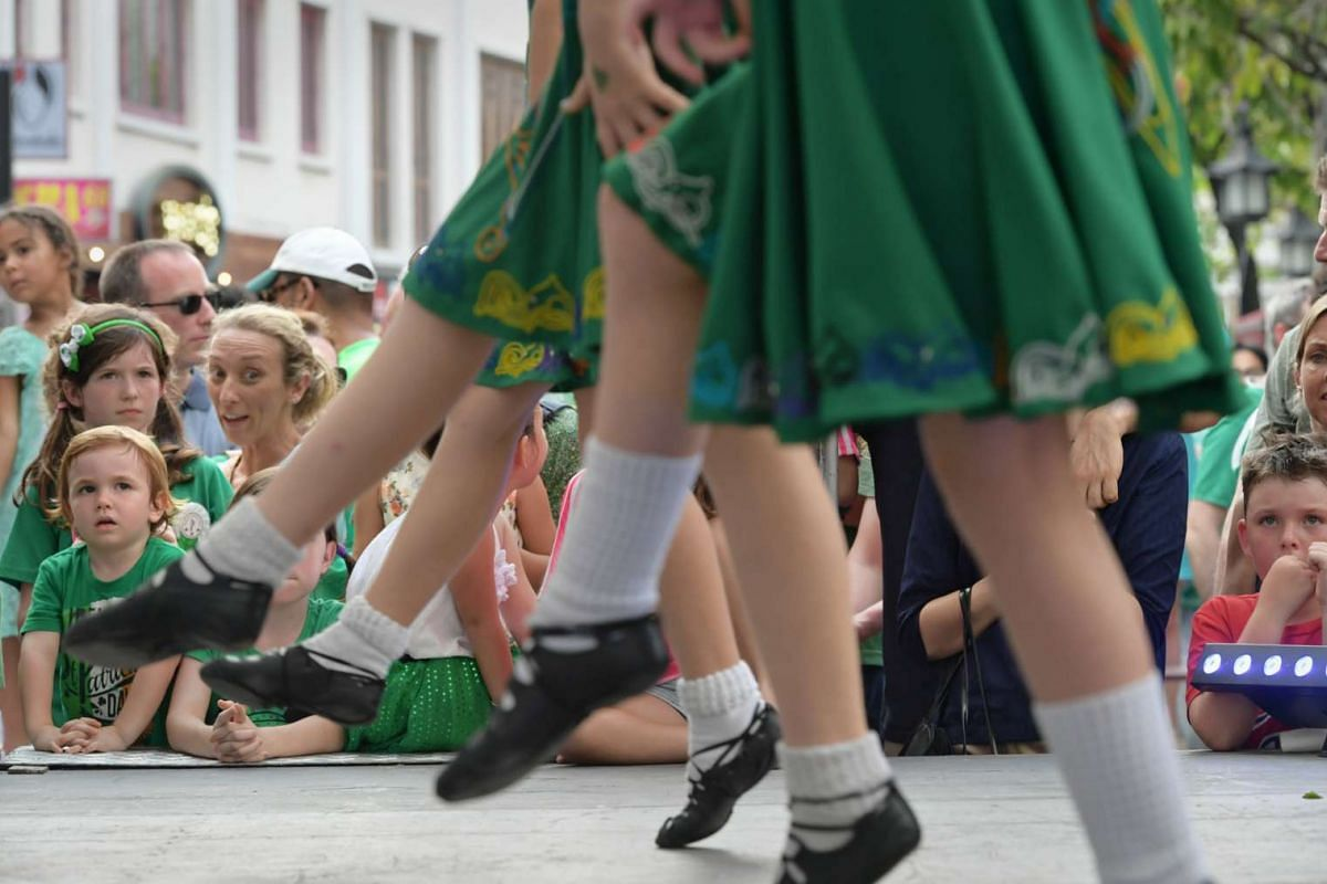 Festival goers at the St. Patrick's Day street festival watch traditional Irish dancers perform on a stage at the junction of Circular Road and Canton Road on March 19, 2017.