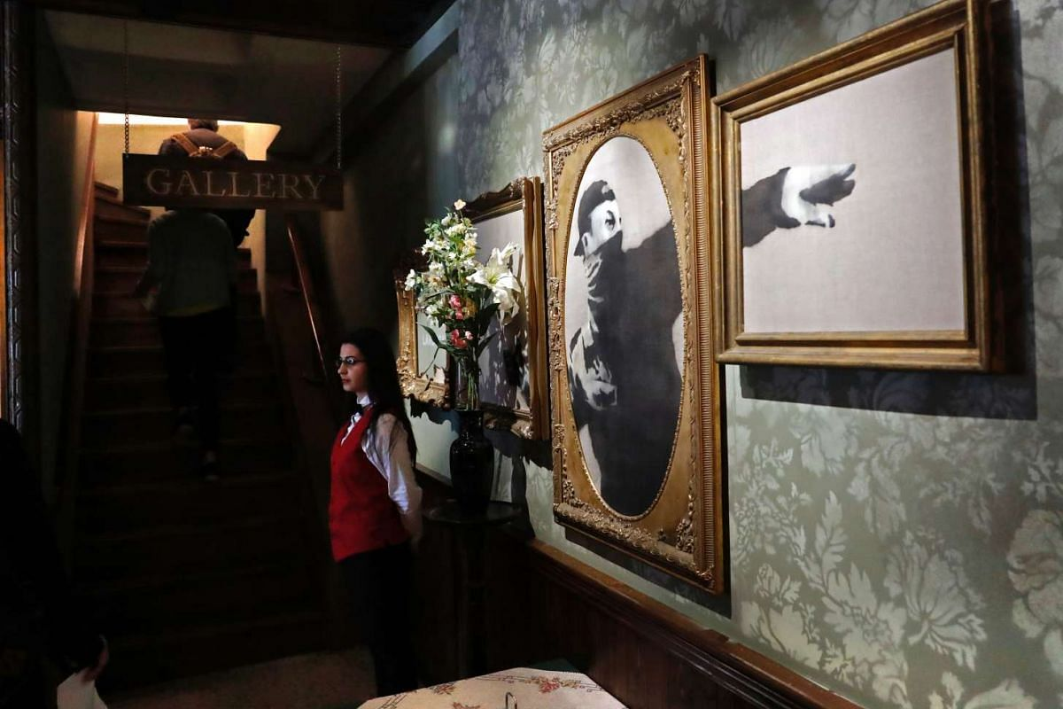 A Palestinian waiter stands inside the lobby at street artist Banksy's newly opened Walled-Off hotel in the Israeli-occupied West Bank town of Bethlehem.