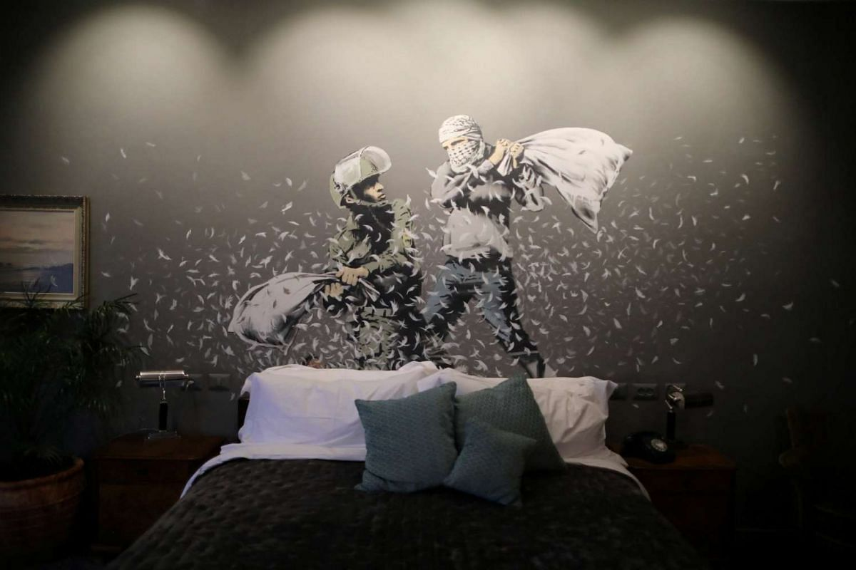A graffiti work painted by street artist Banksy shows an Israeli soldier and masked Palestinian youth having a pillow fight, in the Walled-Off Hotel.